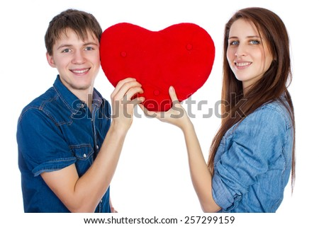 Love a wonderful feeling! Beautiful young happy couple kissing behind a red heart, holding it in hands. Brunettes, girl and boy lovers are isolated on a white background in denim shirt and denim pants - stock photo
