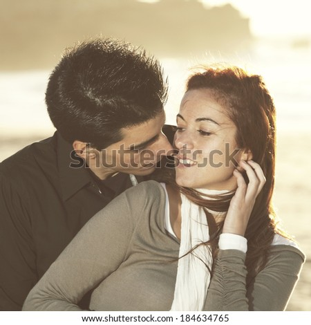Love and affection between a young couple at the beach in sunny day - stock photo