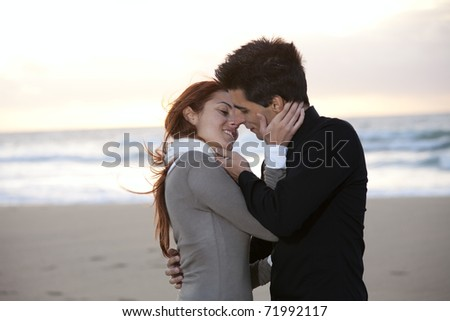 Love and affection between a young couple at the beach in sunny day (selective focus with shallow DOF)