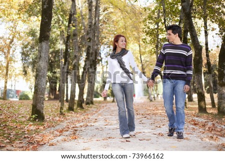 Love and affection between a young couple at the park in autumn season (selective focus with shallow DOF)