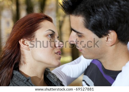 Love and affection between a young couple at the park (selective focus with shallow DOF) - stock photo