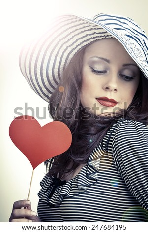 Love and celebrate concept.Beautiful elegant woman in hat holding heart in her hands and smiling. - stock photo