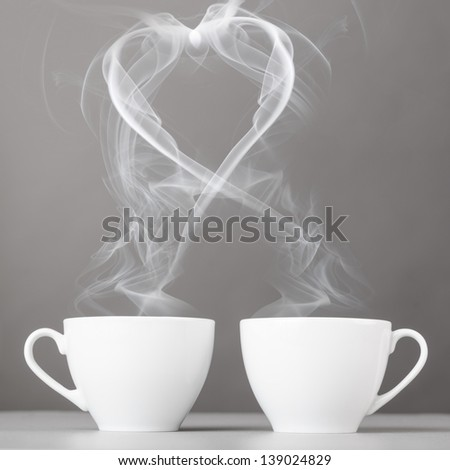 love and coffee. heart silhouette from steaming hot coffee cups - stock photo