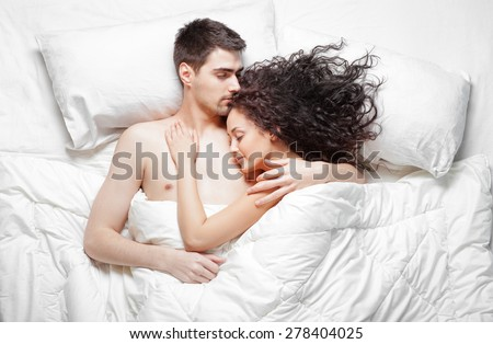 love and comfort overhead of beautiful young couple lying