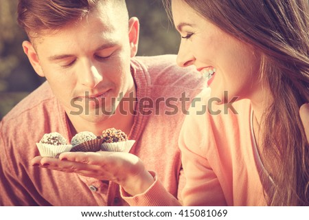 Love and dating. Attractive woman giving cupcakes cookies to handsome man. Happy cute lovers on date outdoor. - stock photo