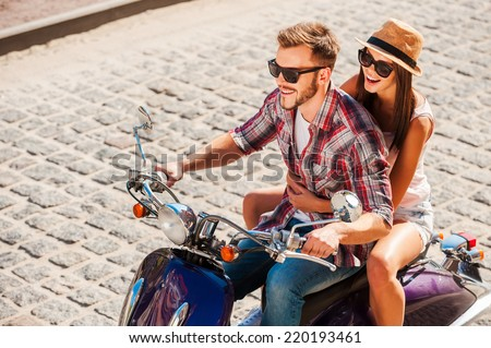 Love and freedom. Top view of beautiful young couple riding scooter together while happy woman bonding to her boyfriend and smiling - stock photo