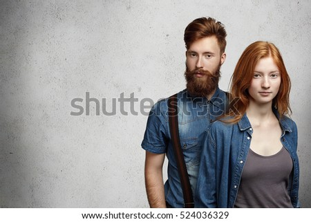 Love and friendship concept. Studio portrait of handsome young hipster with trendy beard wearing denim shirt standing behind beautiful redhead girl, both having serious or sad facial expression