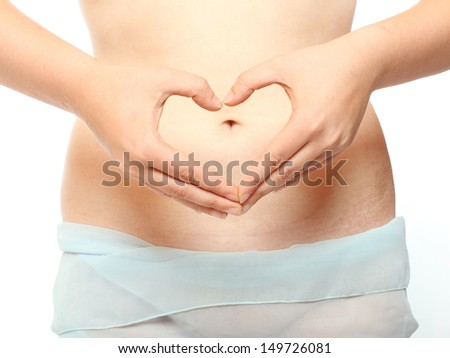 Love and new life concept. A woman's hands forming a heart symbol on belly - isolated on white background.  - stock photo