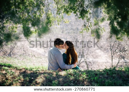 Love and passion. Beautiful young couple kissing while sitting under fir tree against light - stock photo