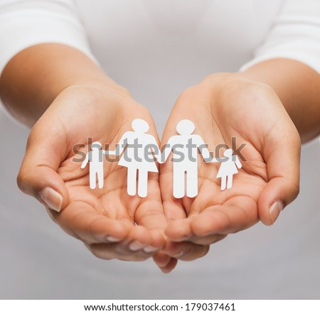 love and relationships concept - closeup of womans cupped hands showing paper man family - stock photo