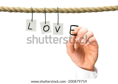 Love and romance concept with the letters L,O,V hanging from a rope across a white background and a mans hand writing the E with a black marker pen, with copyspace. - stock photo