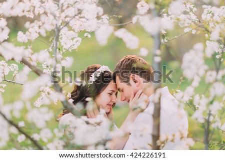 Love and tenderness. Beautiful young loving couple embracing in blossom spring garden. Romantic dating - stock photo