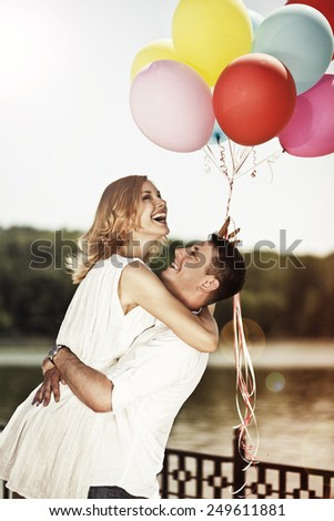 Love and wedding concept. Young attractive happy couple with colorful ballons embracing ang smiling. Man propose woman. - stock photo
