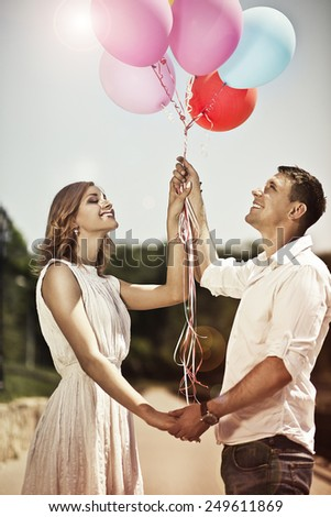 Love and wedding concept. Young happy couple holding in their hands colorful ballons and smiling. - stock photo