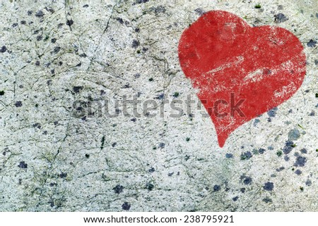 Love background, red heart painted on weathered gray rock surface with small patches of moss and lichen, copy space - stock photo