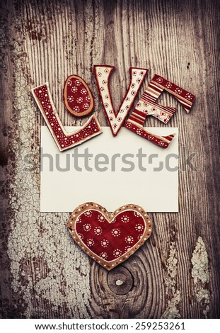love background with paper heart, leeter LOVE and piace of paper as a copy space on wooden background