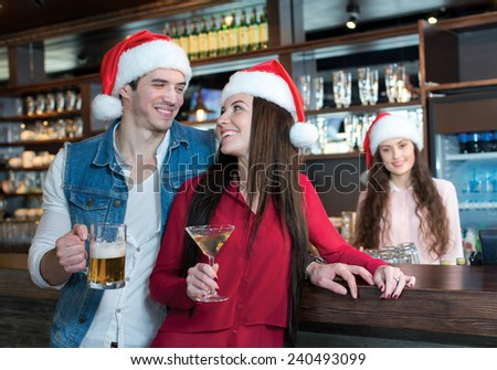 Love beer and Christmas. Loving couple is standing with beer in a bar or pub, wearing New Year Santa Claus hats. Girls bartender also is wearing Santa Christmas hat and stays on a background - stock photo