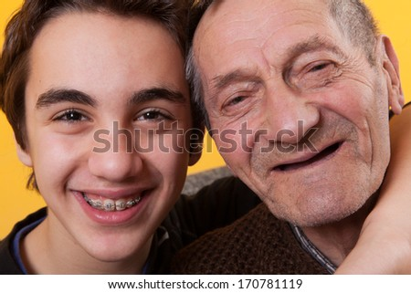 Love between generations. Contrast between the old and the young. Grandson has a denture and grandpa has no teeth. - stock photo