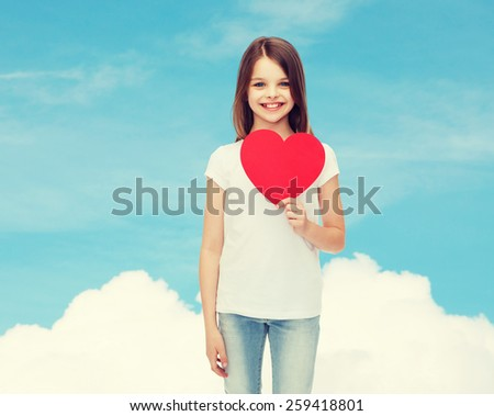 love, charity, childhood and people concept - beautiful little girl sitting at table and holding red heart cutout over blue sky background - stock photo