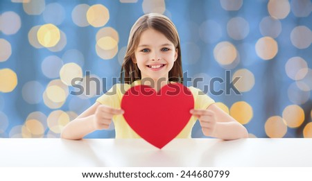 love, charity, holidays, children and people concept - smiling little girl with red heart over blue lights background - stock photo
