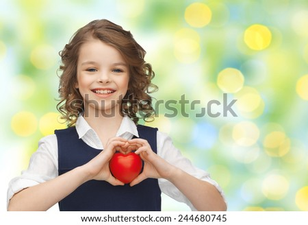 love, charity, holidays, children and people concept - smiling little school girl with red heart over green lights background - stock photo