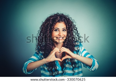 Love. Closeup portrait smiling happy young woman making heart sign, symbol with hands isolated green wall background. Positive human emotion expression feeling life perception attitude body language - stock photo