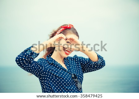 Love. Closeup portrait smiling happy young woman making heart sign, symbol with hands isolated sea scape background. Positive human emotion expression feeling life perception attitude body language - stock photo