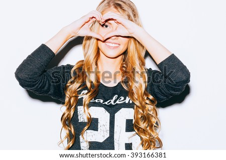 Love. Closeup portrait smiling happy young woman with long blond hair, making heart sign, symbol with hands white wall background. Indoor. Warm color. Hipster. - stock photo