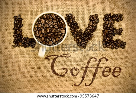 love coffee, coffee beans and mug used to spell love on hessian sack - stock photo