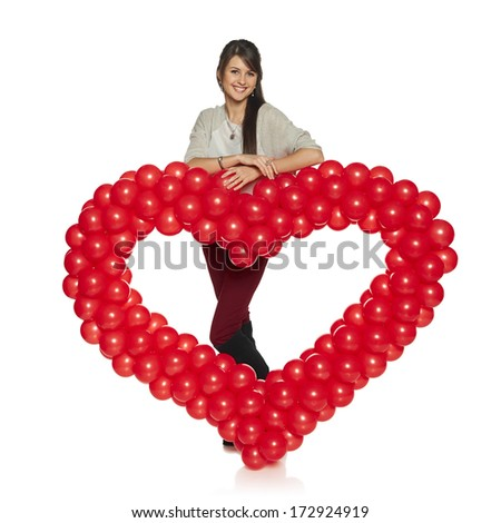 Love concept. Full length smiling woman holding red balloon heart isolated on white background.  Cute beautiful young woman in love.
