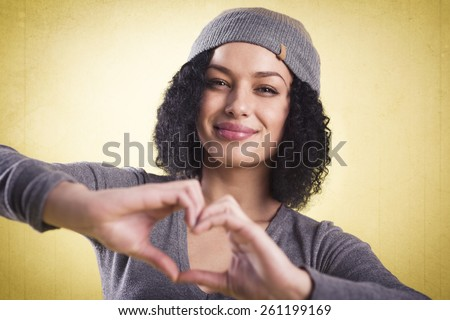 Love concept: Happy girl being cheerful and showing a heart sign with her fingers, isolated on yellow background with copyspace. - stock photo