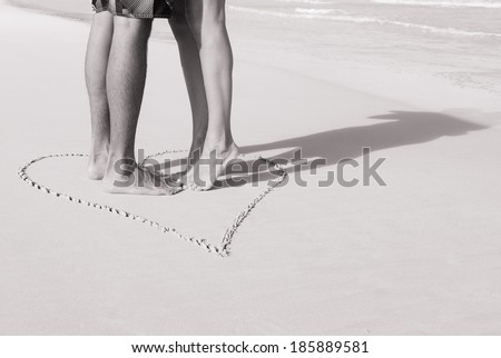 Love concept - Male and female feet in the heart on the beach. Couple kissing on the beach. - stock photo