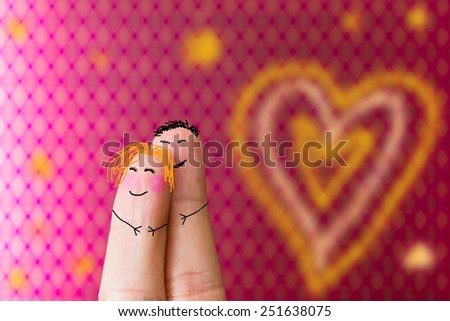 love concept with two fingers with faces over a pink patter background - stock photo