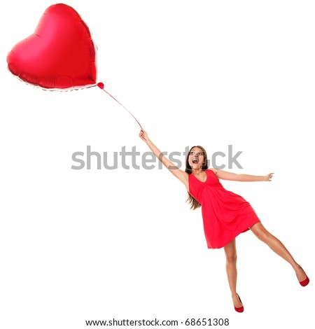 Love concept. Woman flying away with red heart balloon. Funny valentines day image of beautiful cute young woman in red dress. Asian / Caucasian girl isolated on white background in full length. - stock photo