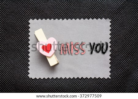 "Love conceptual background with wood clips,love shape on grey paper ""miss you"" - stock photo"