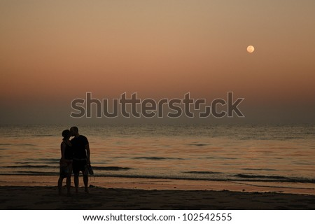 Love couple at sunset with a full moon - stock photo