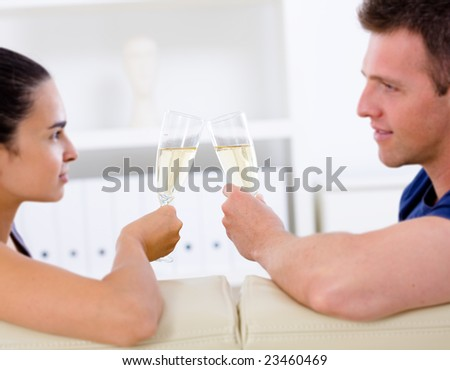 Love couple drinking champagne at home on sofa.