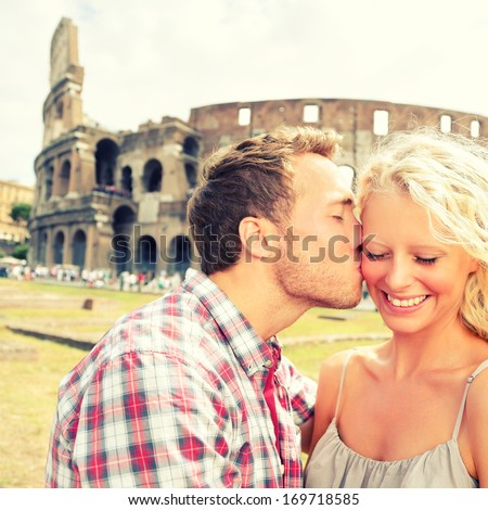 Love - Couple kissing having fun in Rome by the Colosseum. Romantic tourists on holidays vacation travel and man kissing woman on cheek. Beautiful blonde girl and guy in 20s. Coliseum, Rome, Italy. - stock photo
