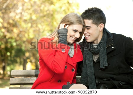 love couple on  sitting on bench, young man whispers to his girlfriend - stock photo