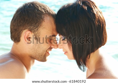 Love couple on the beach against water backdround - stock photo