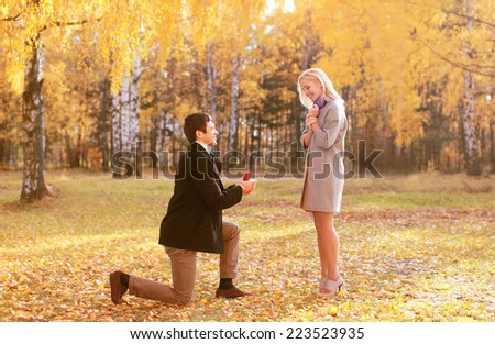 Love, couple, relationship and engagement concept - kneeled man proposing to a woman in the autumn park - stock photo