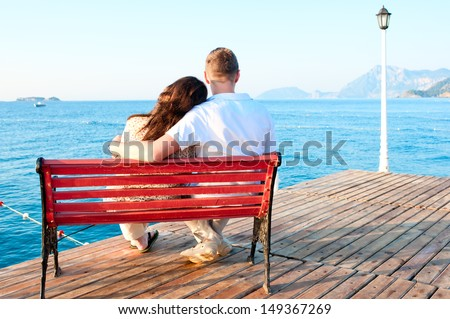 love couple sitting on a bench by the sea embracing - stock photo