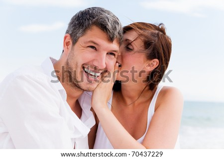Love couple sitting on the beach - stock photo