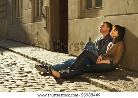 love couple sitting on the pavement - stock photo