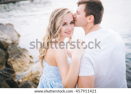 love couple sitting on the rocks by the sea. Couple hugging on the background of blue water. Love story. Couple kissing on the background of the sea.