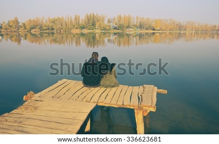 Love Couple Sitting on Wooden Breakwater