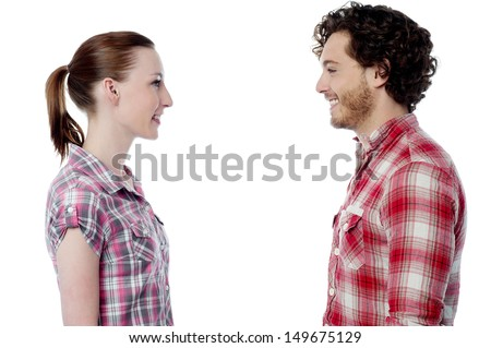 Love couple standing face to face, studio shot. - stock photo
