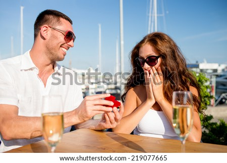 love, dating, people and holidays concept - smiling couple wearing sunglasses with champagne and small red gift box looking to each other at cafe