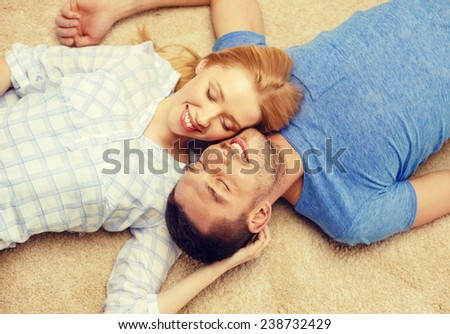 love, family and happiness concept - smiling happy couple lying on floor at home - stock photo