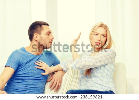 love, family and happiness concept - unhappy couple having argument at home - stock photo